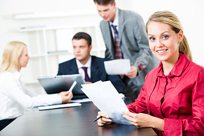 Photo of attractive secretary in red shirt holding paper and looking at camera during business conversation